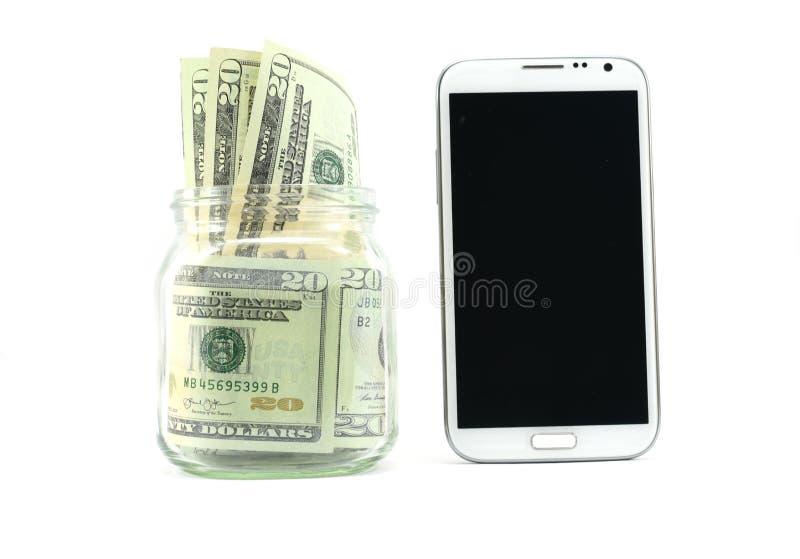 在一个小玻璃瓶子和一个巧妙的电话,投资或花由一种聪明的应用的金钱的概念的美元在电话上 免版税库存照片