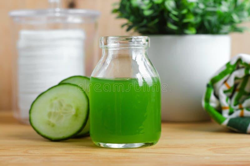 在一个小玻璃瓶子的黄瓜汁准备的自然面部调色剂 自创化妆用品 免版税图库摄影