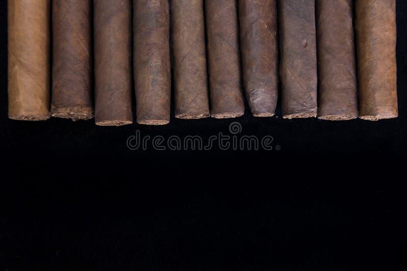 在一个小组的滚动的雪茄在黑色 图库摄影