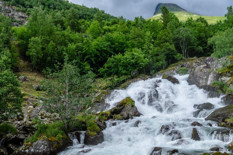 在一个山腰下的美丽的瀑布在挪威 免版税图库摄影
