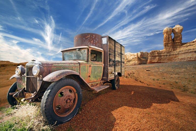 在一个岩石沙漠风景的被放弃的卡车 免版税图库摄影