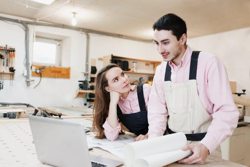 在一个工作台的年轻幸福家庭身分在木匠业车间,写项目 ?? 起始的事务 ?? 免版税库存图片