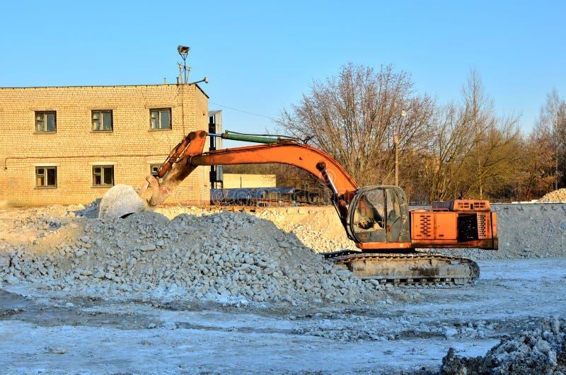 在一个工厂厂房站点的挖掘机工作,与装载者桶的装载的膏药石头 图库摄影