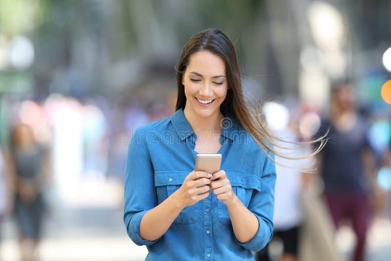 在一个巧妙的电话的愉快的妇女文字消息在街道上 免版税库存照片