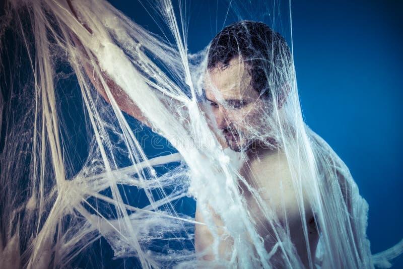 在一个巨大的蜘蛛网困住的被缠结的,赤裸人. 连接数, 例证.图片