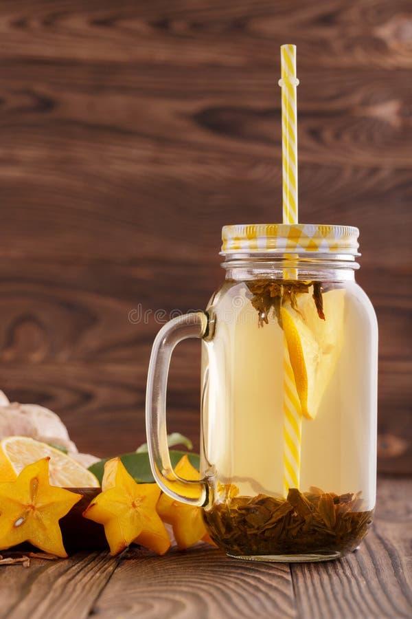在一个巨大的金属螺盖玻璃瓶的健康绿色柠檬茶 冬天饮料 与秸杆的一份饮料 充分新鲜的柑橘水果维生素 复制温泉 免版税库存照片