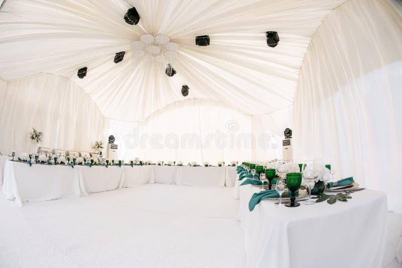 在一个帐篷下的美丽的宴会大厅结婚宴会的 婚礼帐篷装饰的内部准备好客人 图库摄影