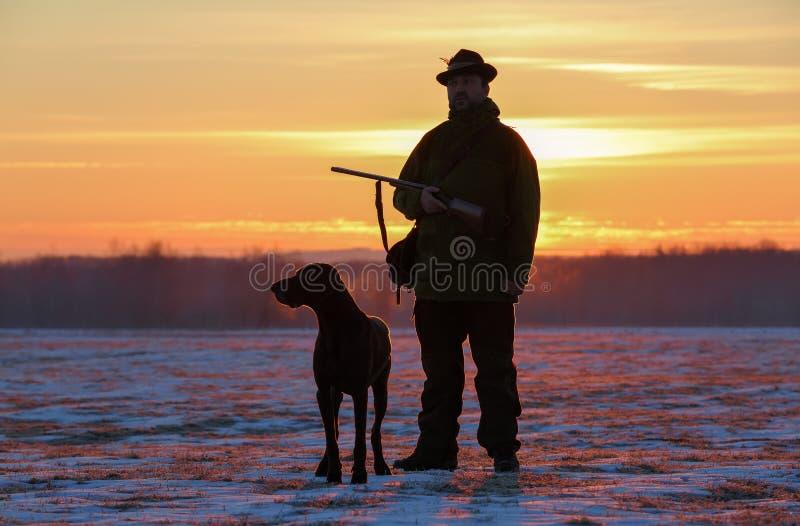 在一个帽子的一位猎人有枪和德国shorthair尖狗品种的在用雪盖的草甸站立 庄严冬天 免版税库存图片