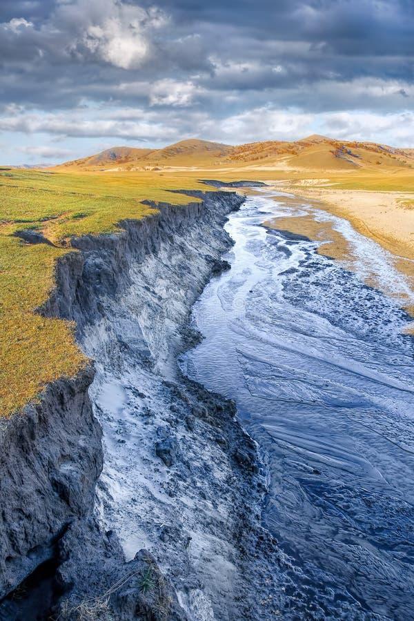 在一个干草原反对剧烈的云彩,内蒙古,中国的土地幻灯片 免版税图库摄影