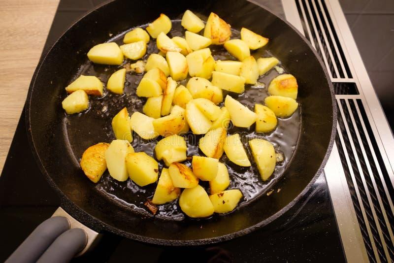 在一个平底锅的油煎的土豆在火炉 免版税库存图片