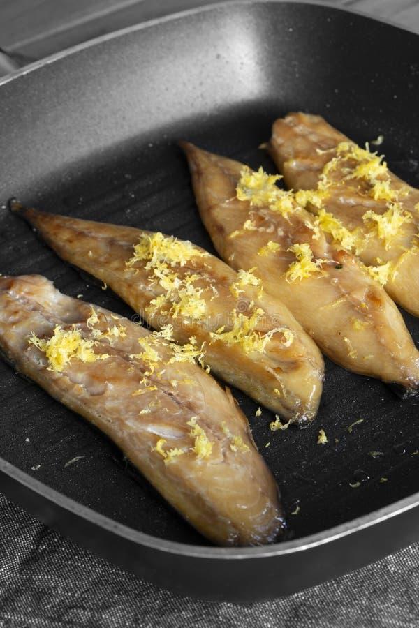 在一个平板炉煎锅的熏制的鲭鱼有在上面的被磨碎的柠檬皮的 图库摄影