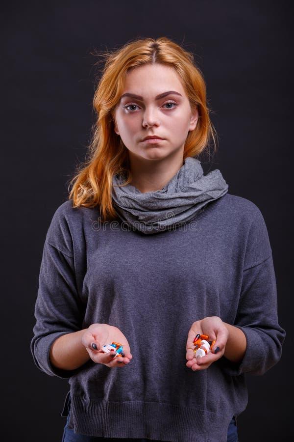 在一个年轻,病的女孩的手上的药片黑背景的 免版税库存图片