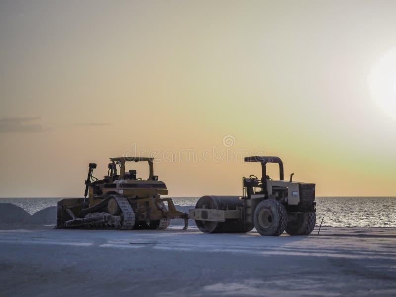 在一个建造场所的两辆重的设备车海岸的 免版税库存照片