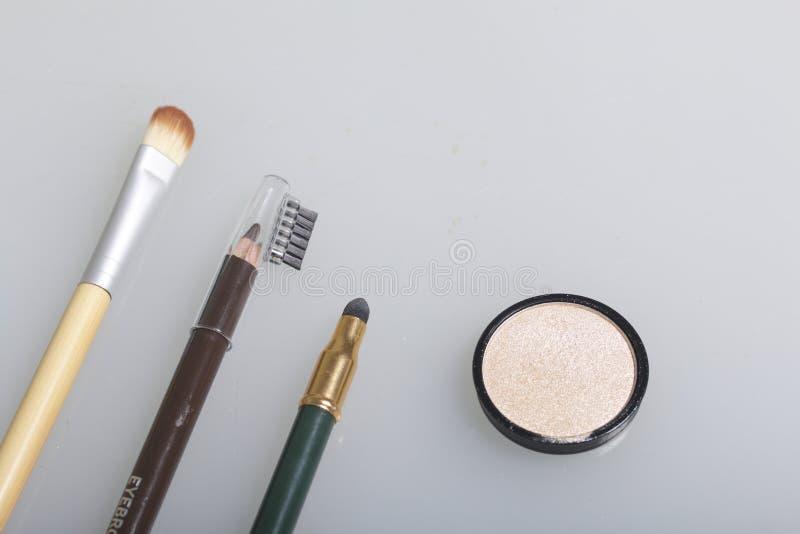 在一个开放瓶子的金黄轮廓色_ 接近应用的化妆用品和化妆铅笔刷子 在白色背景,看法为 库存图片