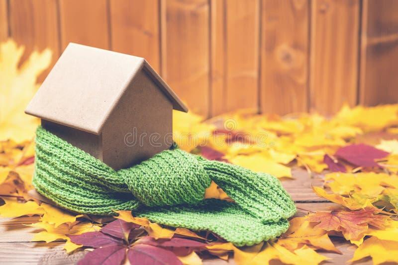 在一个微型房子附近的绿色围巾秋叶背景的 保护或隔绝房子的概念 免版税库存照片
