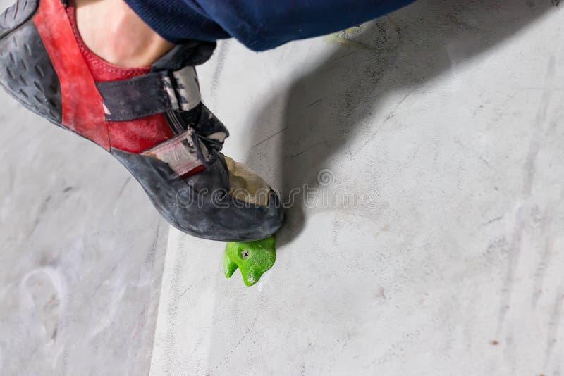 在一个微小,不足的圈套立场的岩石鞋子与袜子的技巧在特写镜头的在上升的墙壁上在屋子里 免版税库存图片