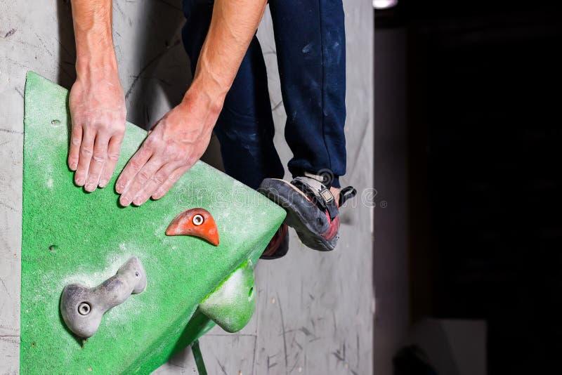 在一个微小,不足的圈套立场的岩石鞋子与袜子的技巧在特写镜头的在上升的墙壁上在屋子里 库存照片