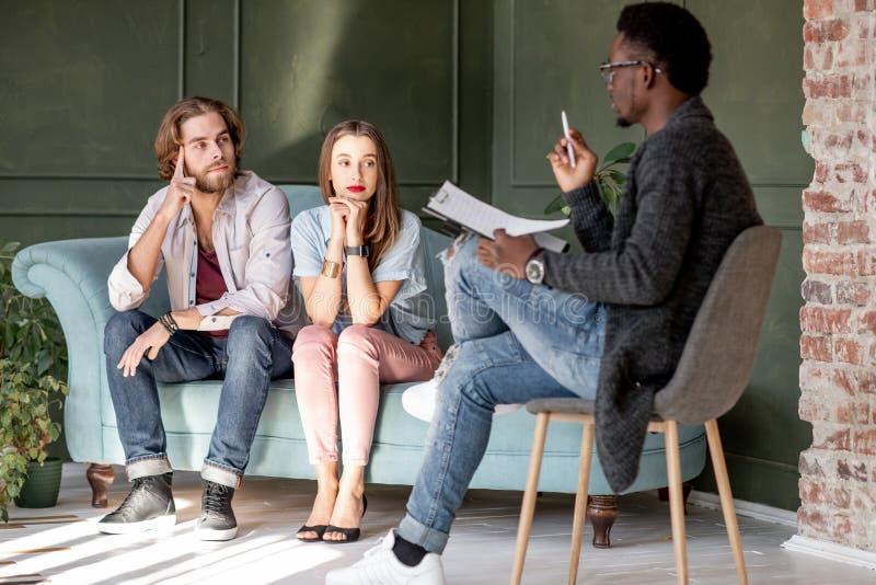 在一个心理会议期间的年轻夫妇与心理学家 免版税库存图片