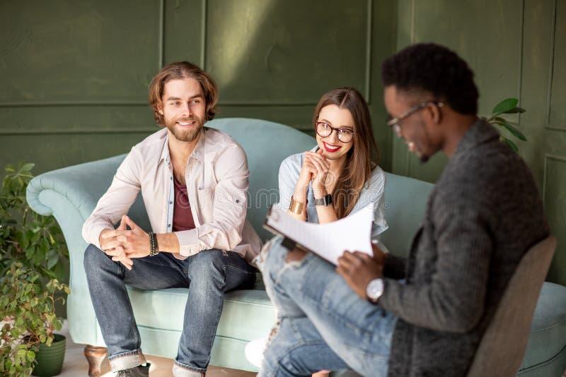 在一个心理会议期间的年轻夫妇与心理学家 库存图片