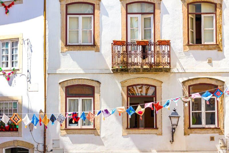 在一个房子前面的装饰五颜六色的垂悬的小垫布在科英布拉 库存图片