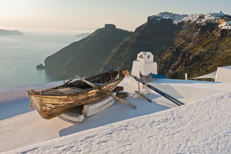 在一个房子屋顶的小船在Skaros岩石前面的日落在Imerovigli村庄,圣托里尼海岛 免版税库存照片