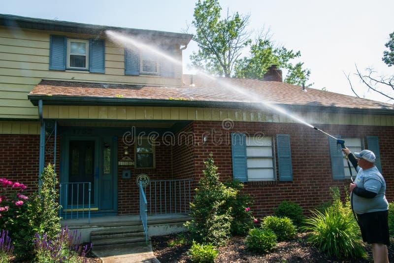 在一个房子的前面的一种重的超重白种人人喷洒的水解答作为他的压力洗涤的服务一部分的 ?treadled 免版税库存照片