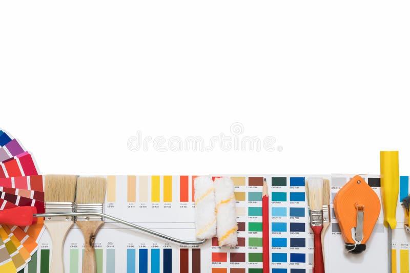 在一个房子项目的专业装饰员图画与工作工具 免版税库存图片