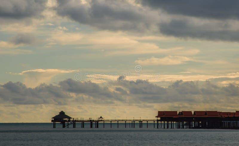 在一个手段海滩的美好的日落在凌家卫岛,马来西亚 太平洋的Overwater高跷垂悬的平房 免版税库存图片