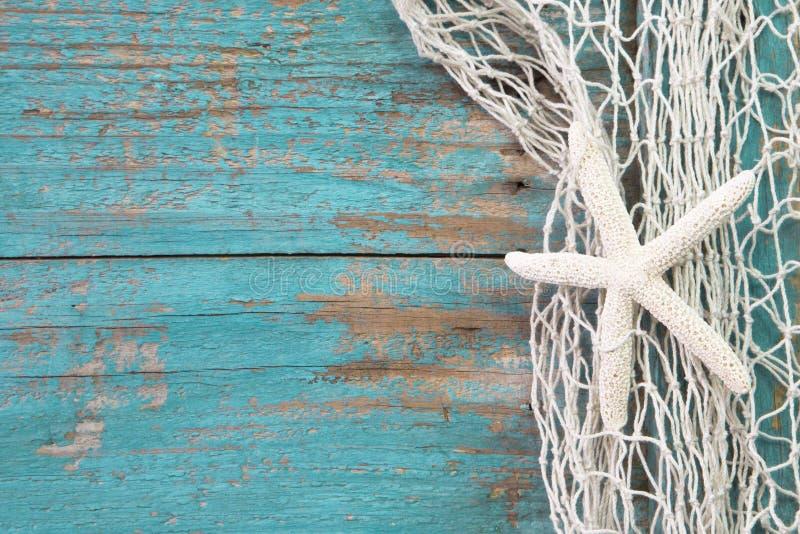 在一个捕鱼网的海星与绿松石木背景sha 图库摄影