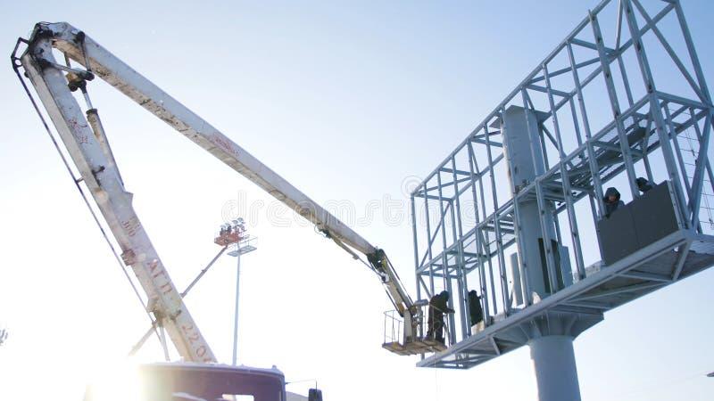 在一个推力平台的建造者在建造场所 人在工作 在建筑工地的建筑工人聚集的绞刑台 库存图片