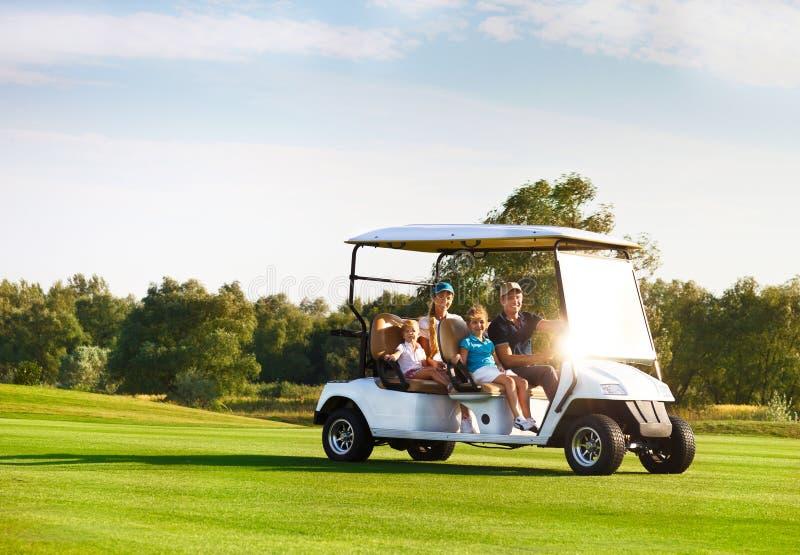 在一个推车的美丽的家庭画象在高尔夫球场 免版税库存照片