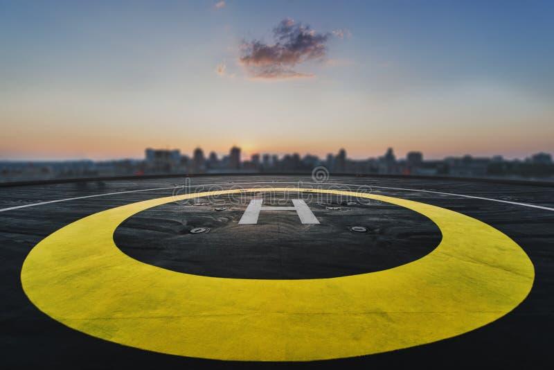 在一个摩天大楼的屋顶的停机坪有都市风景视图 免版税库存图片