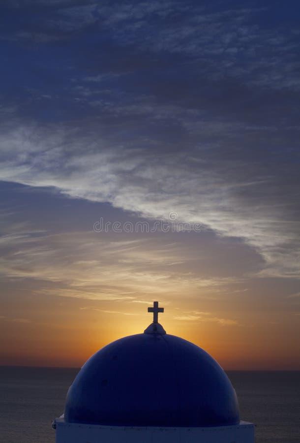 在一个教会的蓝色圆顶的日出在波里Oia附近的在圣托里尼希腊希腊海岛上  免版税库存图片