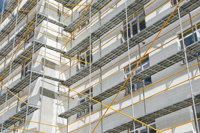 在一个新房、修造的外部、建筑和修理产业、白色墙壁和窗口,黄色管子附近的脚手架 库存照片