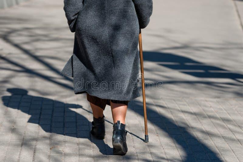 在一个晴天步行沿着向下有走的街道的一个老妇人 免版税库存照片