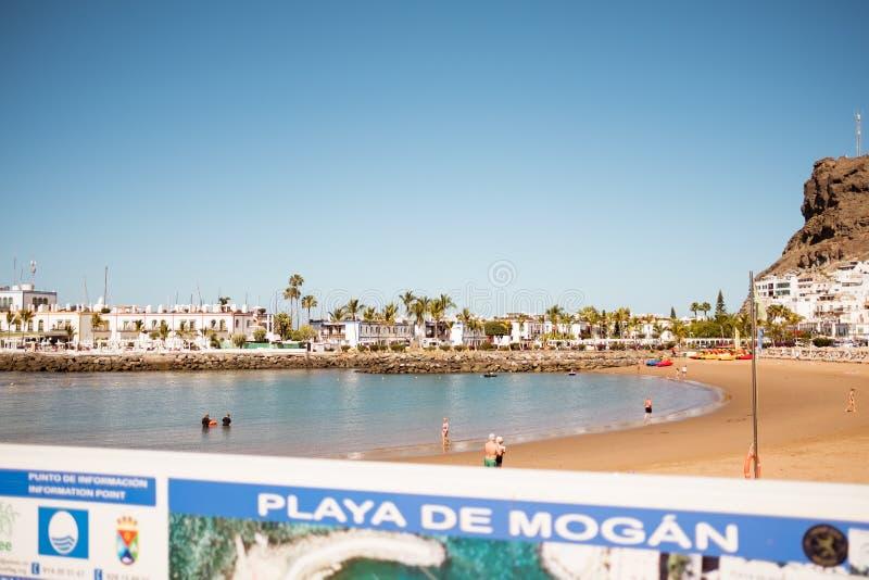在一个晴朗的夏日期间,Puerto de Mogan海滩看法,城市是其中一个最著名的大加那利岛旅游目的地 免版税库存图片