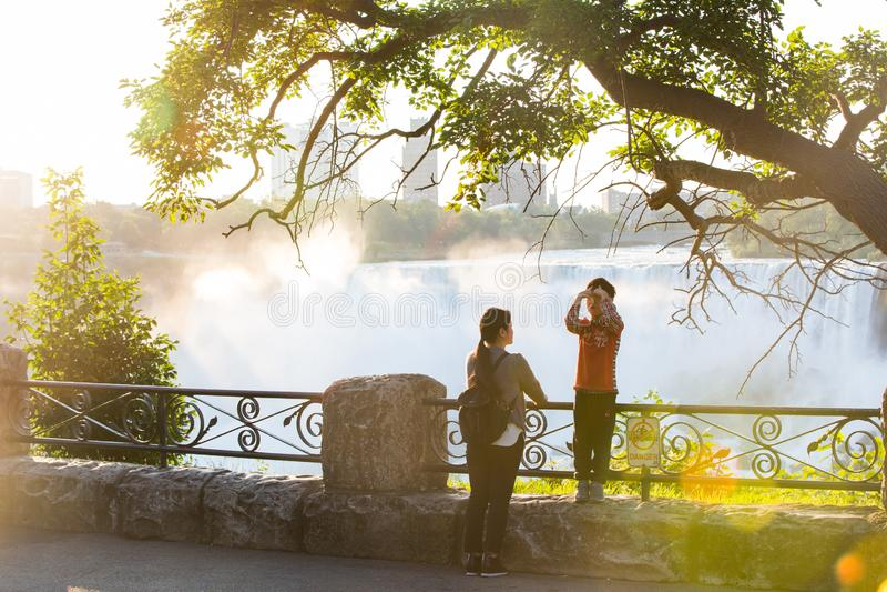 在一个晴朗的早晨,母亲和她的儿子在尼亚加拉瀑布前面的阳光沐浴 库存图片