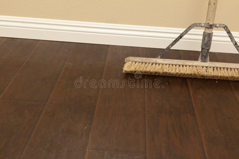 在一个最近安装的层压制品的地板和护壁板上的推式路帚 免版税库存照片