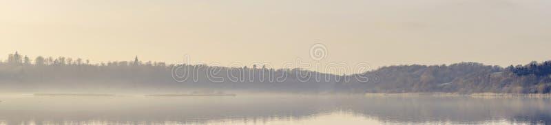 在一个有薄雾的湖的全景视图早晨太阳的 库存图片