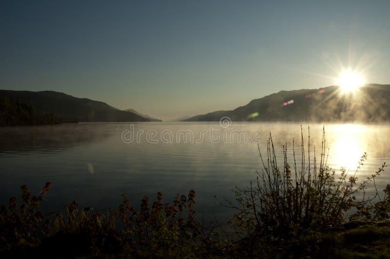 在一个有薄雾的湖的日出 库存照片