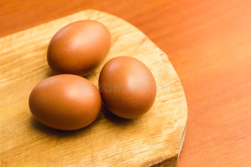 在一个木切板的三个棕色鸡鸡蛋 免版税库存照片