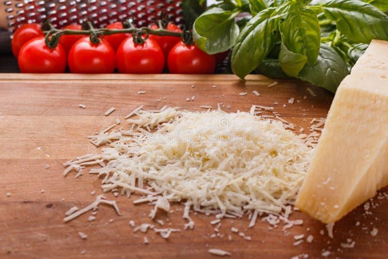 在一个木切的委员会的芬芳被磨碎的巴马干酪 免版税库存照片