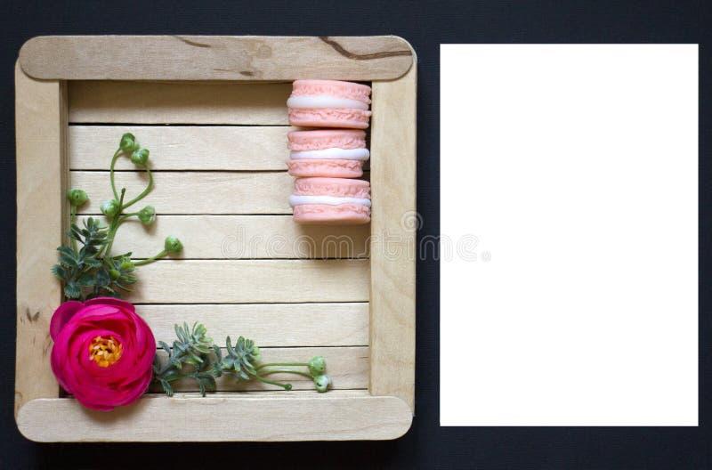 在一个木制框架的桃红色花 在黑背景的木制框架 在木背景的蛋白杏仁饼干 免版税库存图片