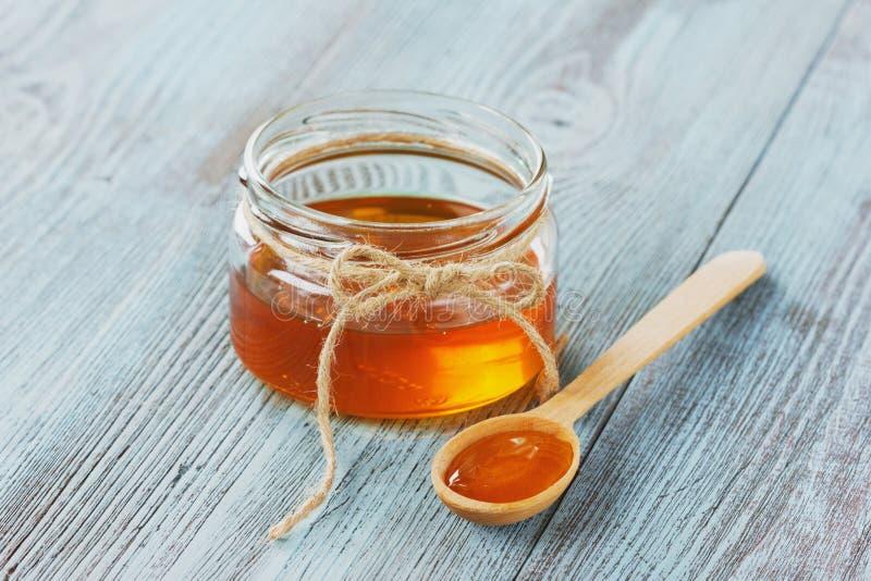 在一个木匙子和瓶子的蜂蜜 免版税库存照片