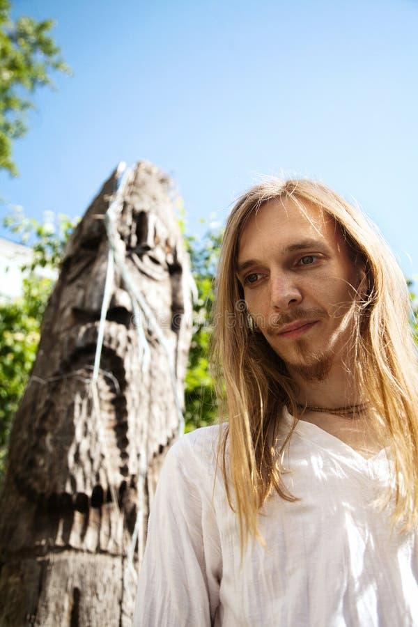在一个木杆神象雕塑旁边的斯拉夫的异教的年轻长发人 库存图片