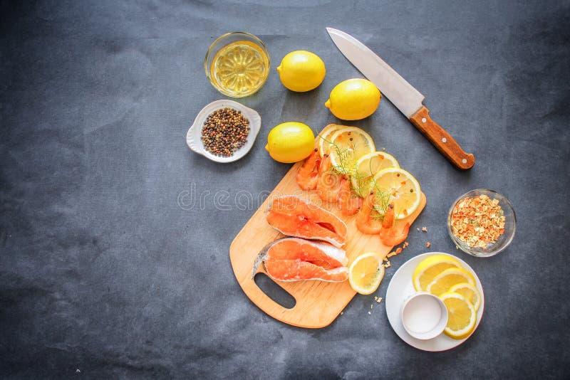 在一个木板上计划了三文鱼未加工的虾绿色柠檬切片盐调味料胡椒和一把刀子烹调的 免版税库存图片