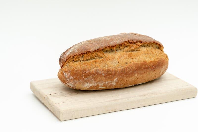 在一个木板的新近地被烘烤的面包谎言 库存照片