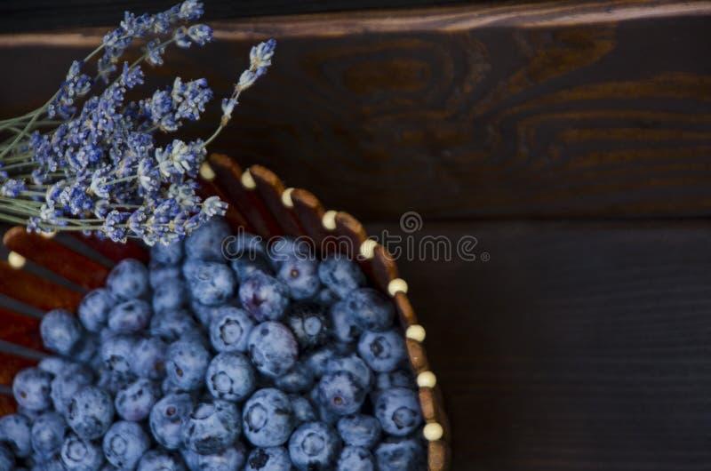 在一个木板的新鲜的蓝莓,黑暗的背景 淡紫色 r 库存图片