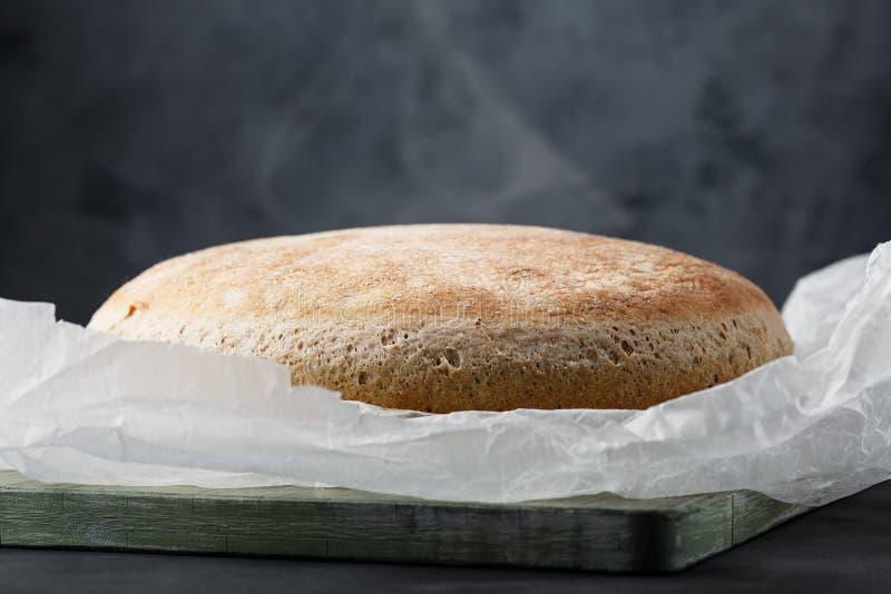 在一个木板的新鲜的被烘烤的面包 在木切板的传统圆的工匠黑麦面包大面包面粉 ?? 免版税库存图片