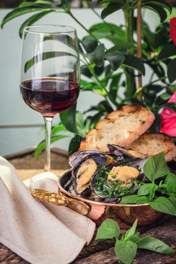 在一个木板的煮熟的淡菜有一杯的酒 库存照片